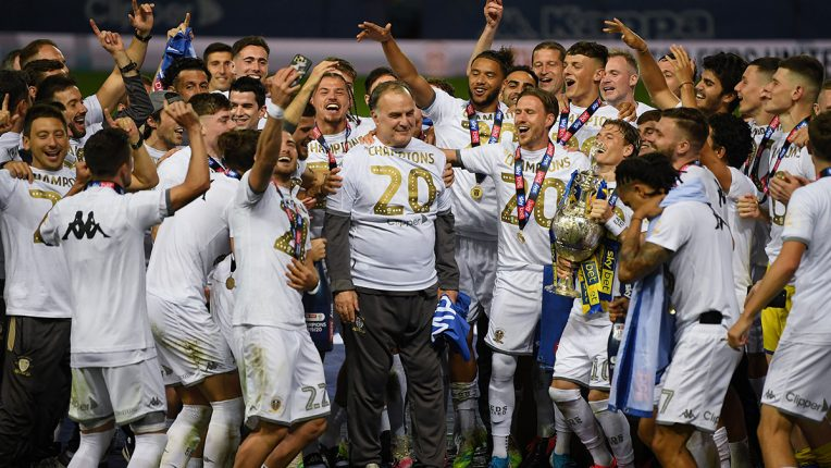 Marcelo Bielsa is surrounded by his Leeds squad as they celebrate winning the Championship