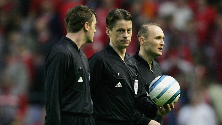 Lubos Michel (centre) and his assistants walk off at half-time at Anfield