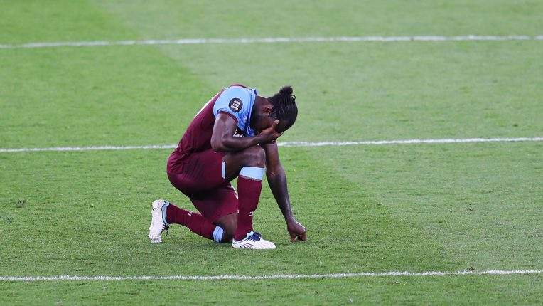 West Ham's Michail Antonio kneels on the turf after losing to Tottenham