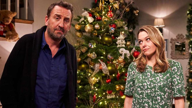Lee Mack and Sally Bretton pose by a Christmas tree for the Not Going Out Christmas Special 2020