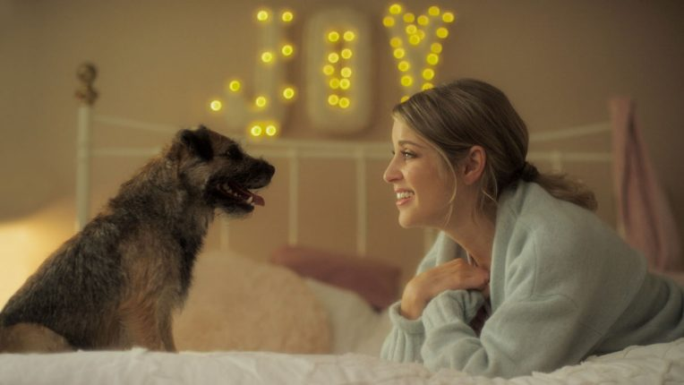 Joy on her bed with her pet dog in new Amy Huberman comedy Finding Joy