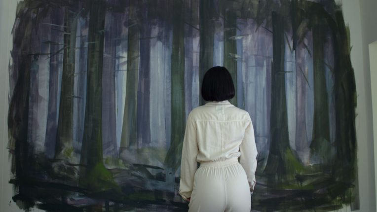 Eve Hewson as Adele in Behind Her Eyes staring at a painting of trees