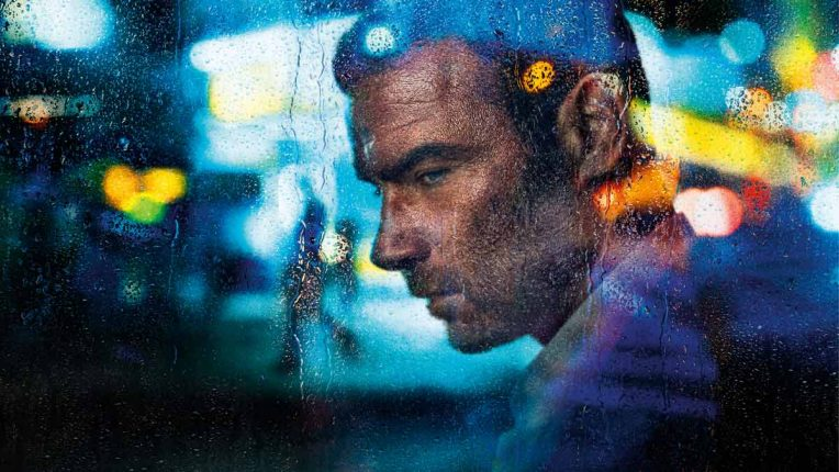 A battered and tired Ray Donovan in the back of a car, played by Liev Schreiber