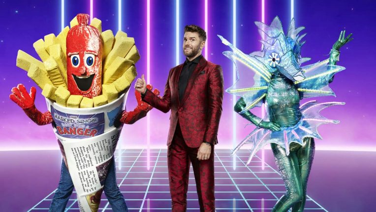 Joel Dommett with two performers on The Masked Singer series 2